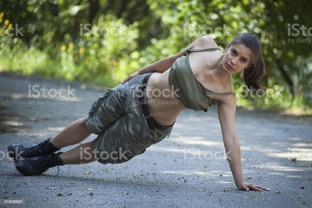 Beautiful military woman training in park - pushups stock photo