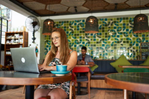 Beautiful millennial woman typing on laptop sitting at table in bohemian cafe in Bali Indonesia stock photo