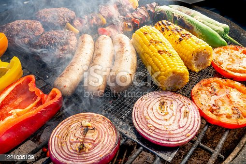 Peppers, Green Chilis, Corn, Onion, Hamburgers, Brats, and Kabobs arranged on a charcoal grill