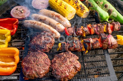 Peppers, Green Chilies, Corn, Onion, Hamburgers, Brats, and Kabobs arranged on a charcoal grill