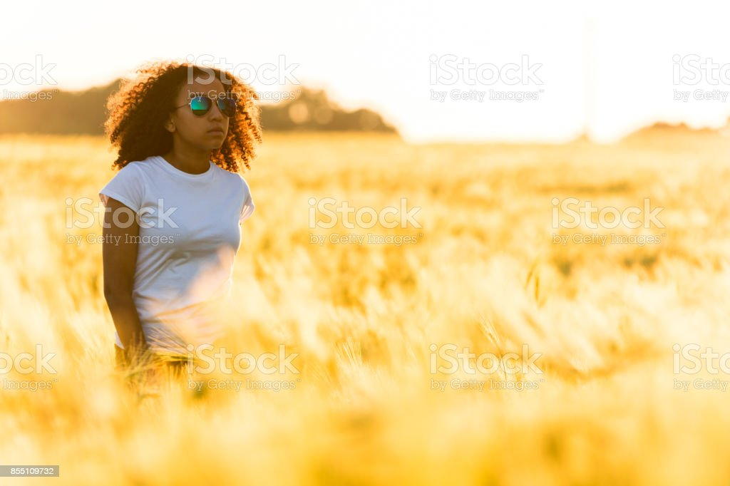 A beautiful mixed race African American female teenager young woman standing in a wheat field at sunset in golden sunshine wearing sunglasses and white t-shirt stock photo