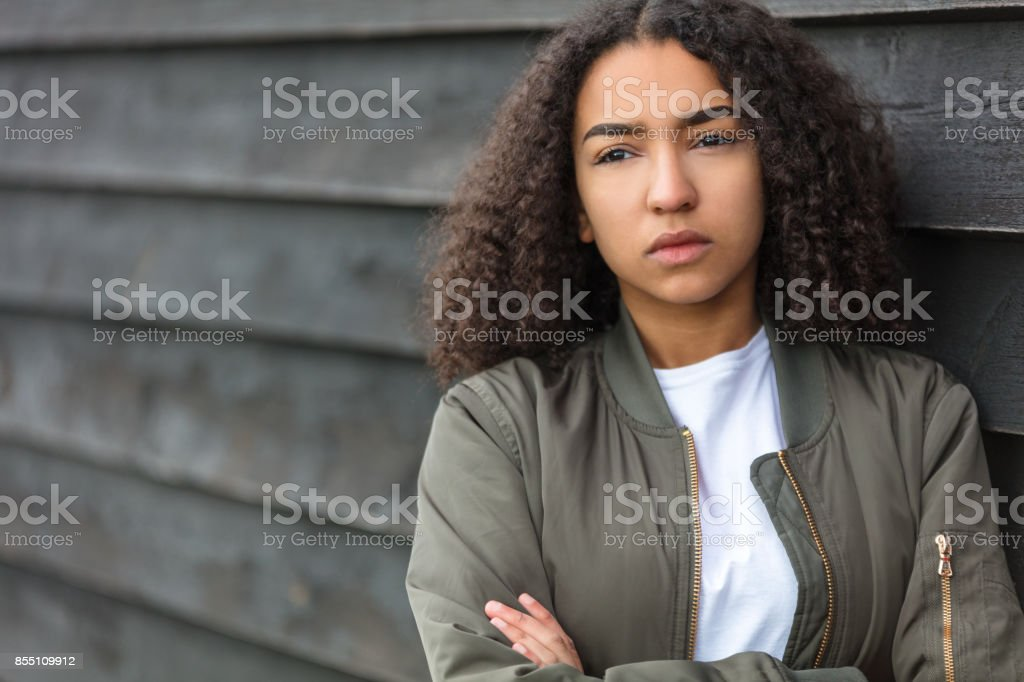 Beautiful mixed race African American girl teenager female young woman outside wearing a green bomber jacket looking sad depressed or thoughtful stock photo