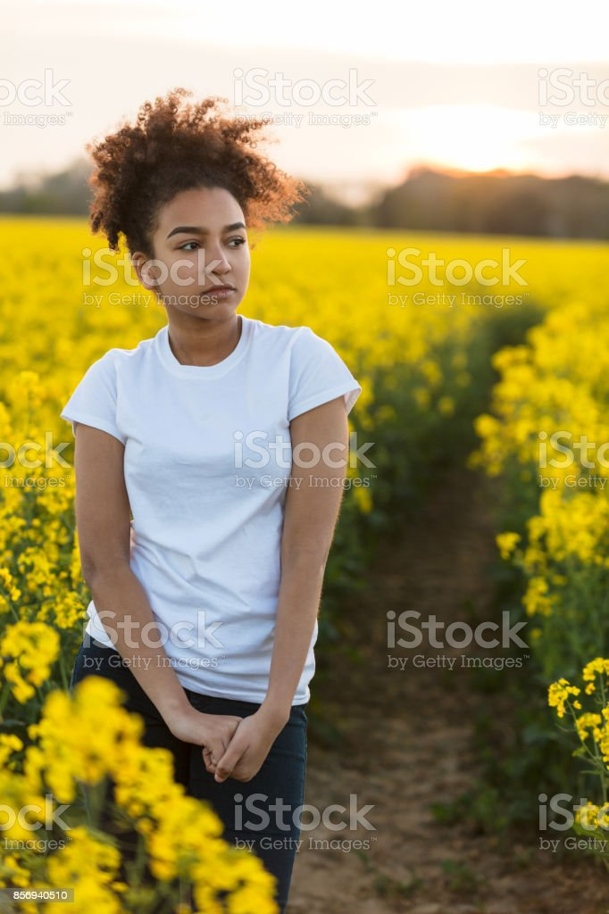 Beautiful mixed race African American girl teenager female young woman outside on a path in a field of yellow flowers looking scared sad depressed or thoughtful stock photo