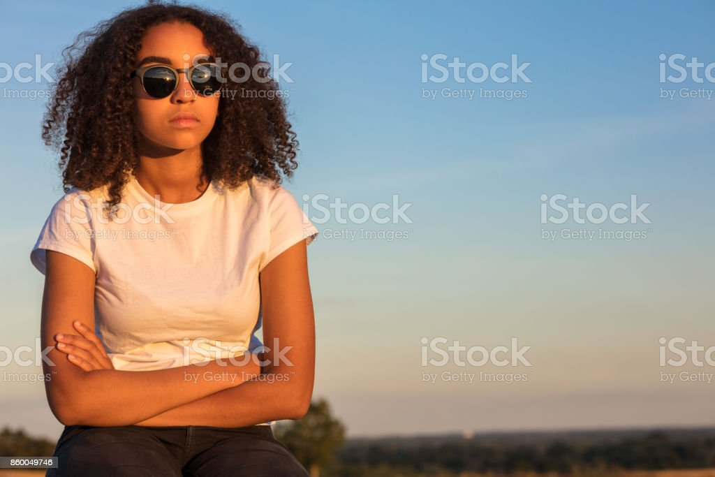 Beautiful mixed race African American girl teenager female young woman outside wearing sunglasses looking sad depressed or thoughtful at sunrise or sunset stock photo