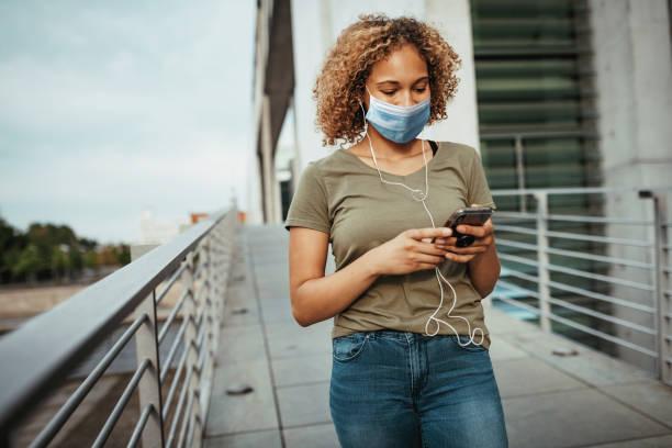 mooi gemengd rasmeisje dat met gezichtsmasker in openlucht glimlacht - podcast stockfoto's en -beelden