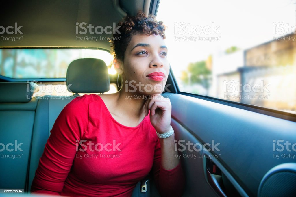 Beautiful mixed race millennial female smiling in car looking at the view stock photo