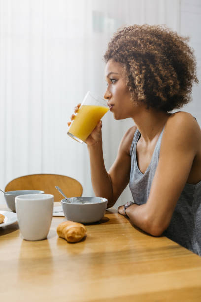 Beautiful mixed race woman drinking a glass of orange juice at  home stock photo