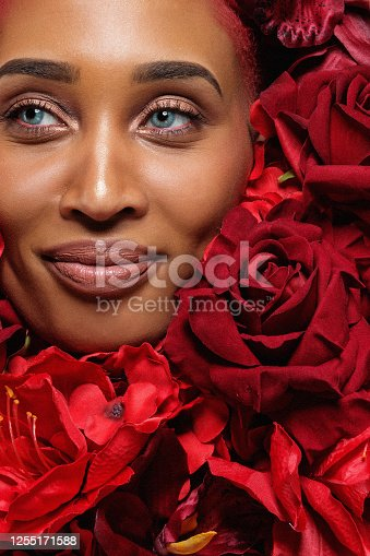 A beautiful mixed race woman's female face laying in a colourful bed of red roses and other flowers