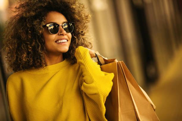 bela mistura corrida mulher segurando sacolas de compras e sorrindo - mercadoria - fotografias e filmes do acervo