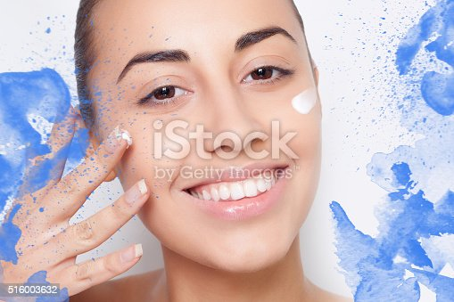 istock beautiful model applying cosmetic cream treatment on her face white 516003632
