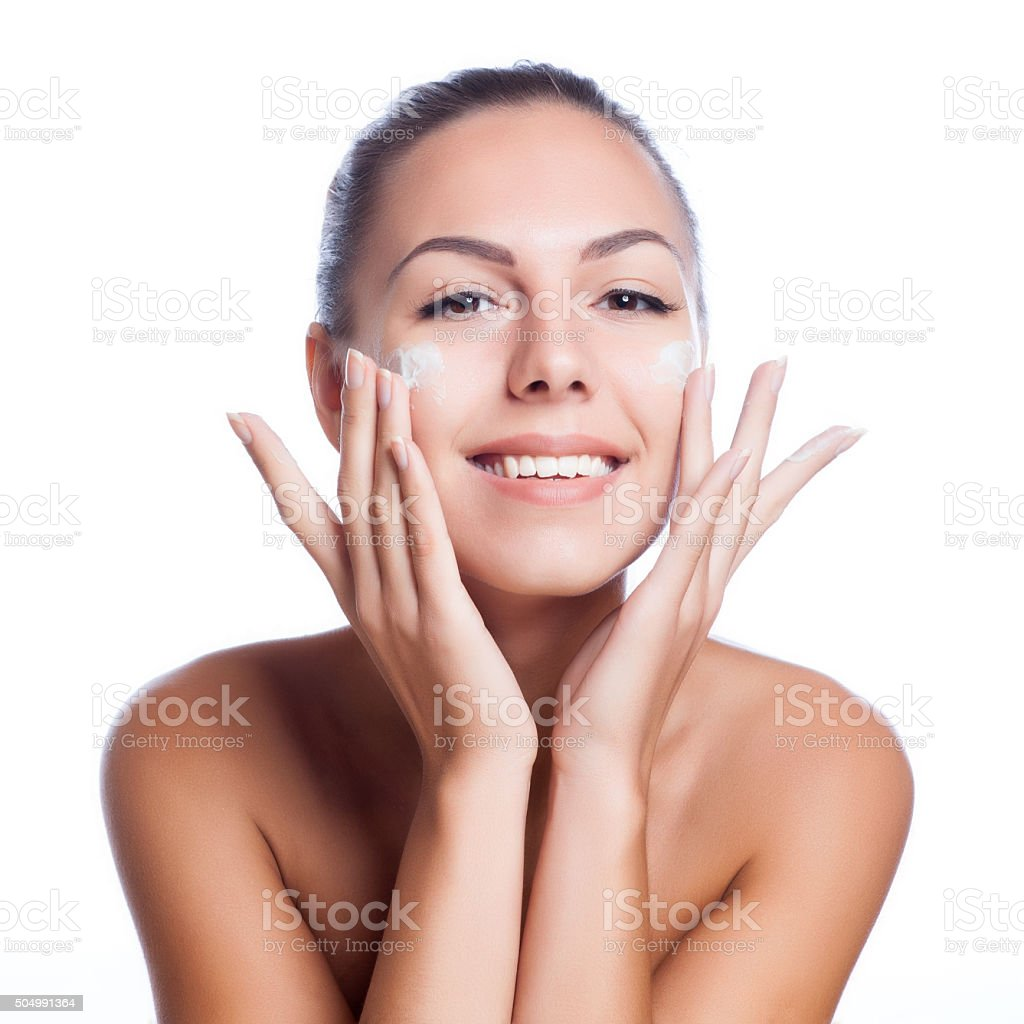 beautiful model applying  cream treatment on her face on white stock photo