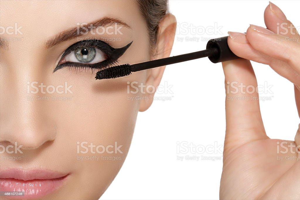 Beautiful model applying mascara on eyelashes  close up stock photo
