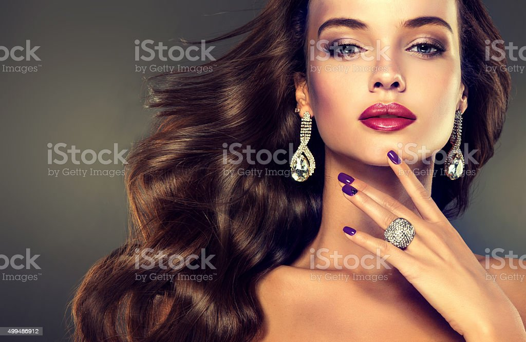 Beautiful model brunette with long curled hair. Luxury fashion style, stock photo