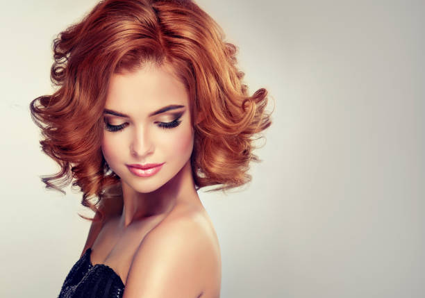 Beautiful model brunette with middle length curled hair and bright make up. stock photo