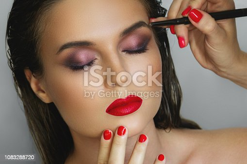 istock Beautiful model during work with a professional make-up artist 1083288720