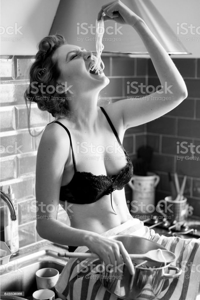 beautiful model eats spaghetti with the hands stock photo