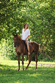 Beautiful equestrian girl ride horseback in summer woods at sunset