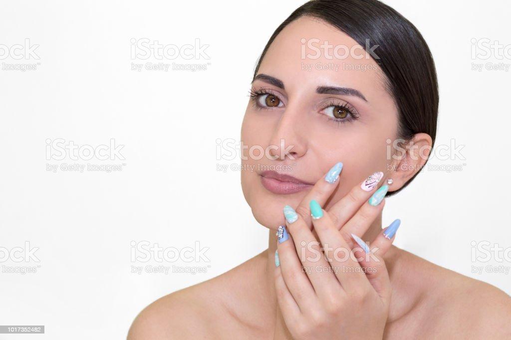 Beautiful model girl with blue manicure nail design rhinestones stock photo