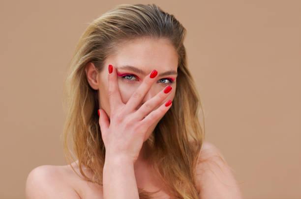 Hermosa chica modelo con manicura roja en las uñas con maquillaje brillante y cosméticos - foto de stock