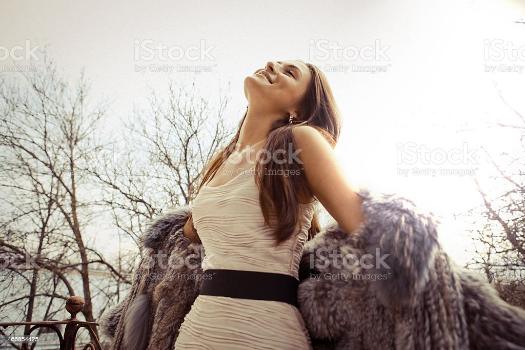 Beautiful model in white dress and fur coat stock photo