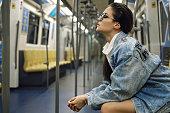 Beautiful model is posing in carriage of metro train