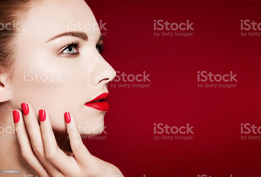 Beautiful model profile closeup beauty. Red manicured nails and lips. stock photo