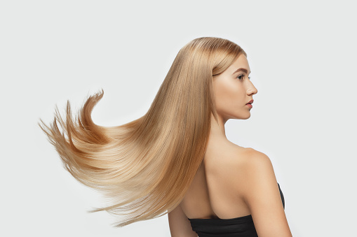 Wave. Beautiful model with long smooth, flying blonde hair on white studio background. Young caucasian model with well-kept skin and hair blowing on air. Concept of salon care, beauty, fashion.