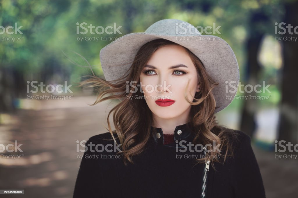 Beautiful Model Woman on Greenery Background Outdoors. Makeup, Hairstyle, a Grey Hat stock photo