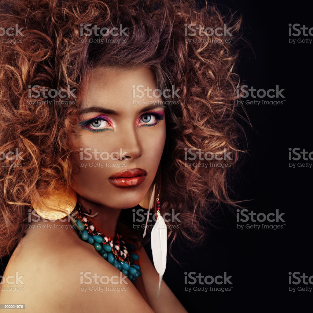 Beautiful Model Woman with Curly Hair, Makeup and Dark Bronze Skin on Black Background - Stock image .