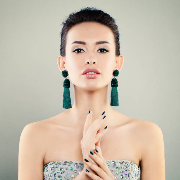 beautiful model woman with makeup, manicure and green earrings. cute young face - prom fashion stock photos and pictures