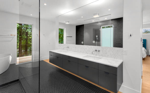 Beautiful modern bathroom interior in new luxury home with double vanity, mirror, and cabinets stock photo