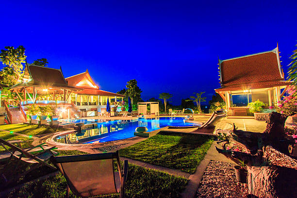 beautiful modern getaway resort with pool at night - competition group stock photos and pictures