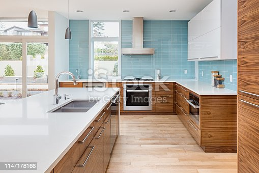 istock beautiful modern kitchen in new contemporary style luxury home, with island, pendant lights, hardwood floors, and stainless steel appliances. Features blue tone tile that extends to the ceiling 1147178166
