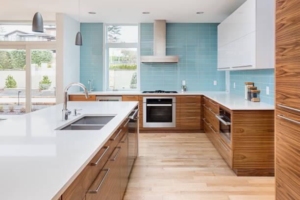 섬, 펜 던 트 조명, 나무 바닥 및 스테인레스 스틸 가전 제품과 함께 새로운 현대적인 스타일의 고급 주택에 아름 다운 현대 부엌. 천장에 확장 블루 톤 타일을 갖추고 있습니다 - 모던 양식 뉴스 사진 이미지