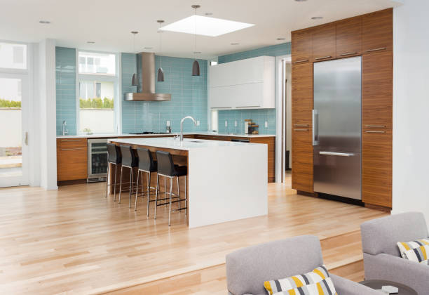 beautiful modern kitchen in new contemporary style luxury home, with island, pendant lights, hardwood floors, and stainless steel appliances. Features blue tone tile that extends to the ceiling stock photo