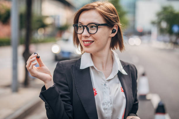 Beautiful modern lady with wireless headphones downtown One woman, beautiful young businesswoman standing on the street downtown, using wireless headphones. wireless headphones stock pictures, royalty-free photos & images