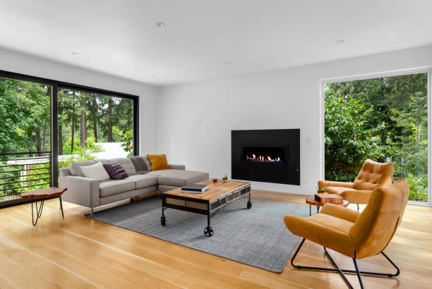 Beautiful modern living room interior with hardwood floors and fireplace in new luxury home. Features large windows with view of trees and abundant natural light. stock photo