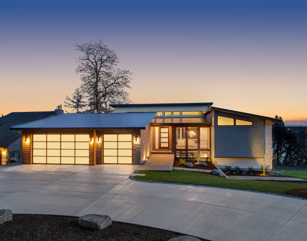 Beautiful modern luxury home exterior at sunset. Features contemporary design and three car garage facade of home with manicured lawn, and backdrop of trees and dark blue sky home exterior stock pictures, royalty-free photos & images