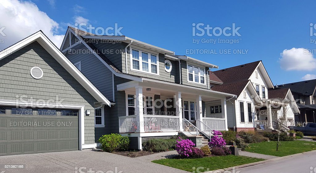 Residential street with new modern 2 level homes and garages. Small...