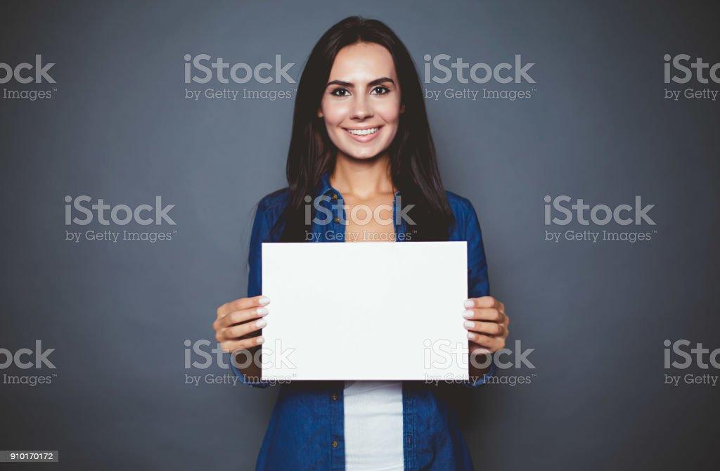 Linda mulher sorridente moderna uma camisa jeans com uma folha em branco do papel para a publicidade nas mãos sobre um fundo cinza isolado. foto de stock royalty-free