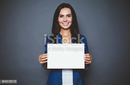 istock Beautiful modern smiling woman in a jeans shirt with blank sheet of paper for advertising in hands on a gray background isolated. 910170172