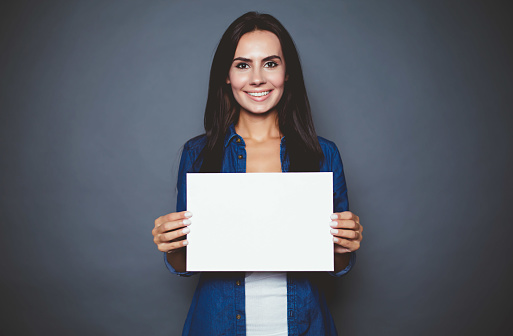 Beautiful modern smiling woman in a jeans shirt with blank sheet of paper for advertising in hands on a gray background isolated.