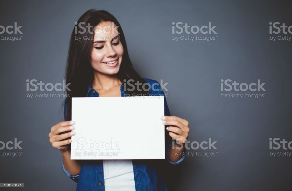 Beautiful modern smiling woman in a jeans shirt with blank sheet of paper for advertising in hands on a gray background isolated. stock photo
