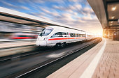 Beautiful modern train in motion on railway station at sunset. White train on railroad track with motion blur effect in Europe in evening. Railway platform. Industrial landscape. Railway tourism