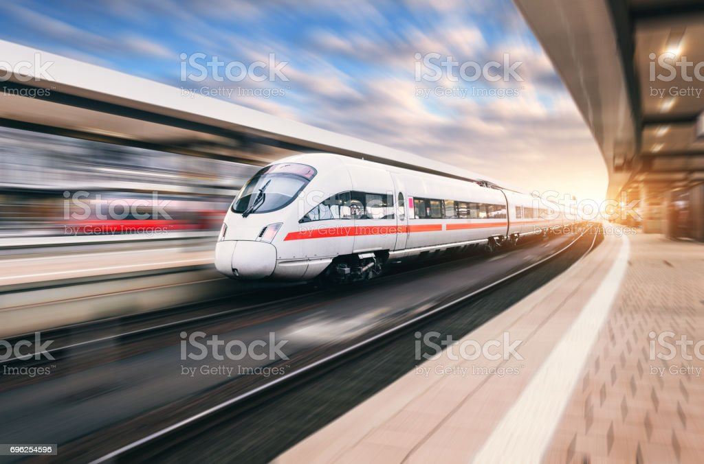 Beautiful modern train in motion on railway station at sunset. White train on railroad track with motion blur effect in Europe in evening. Railway platform. Industrial landscape. Railway tourism stock photo