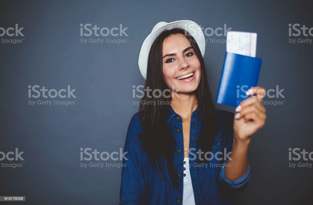 Beautiful modern young woman with a passport and air tickets in her hand in  denim shirt on a gray background is isolated. stock photo