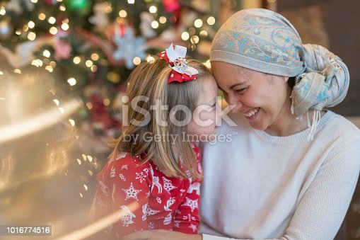 A beautiful ethnic mom wearing a headcovering and battling cancer holds her young daughter playfully on her lap by the Christmas tree in their living room. They're bumping their foreheads together affectionately.