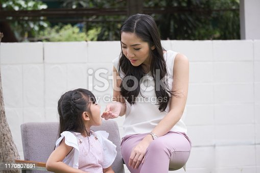 istock Beautiful mom is trying to feeding food for her daughter. 1170807691