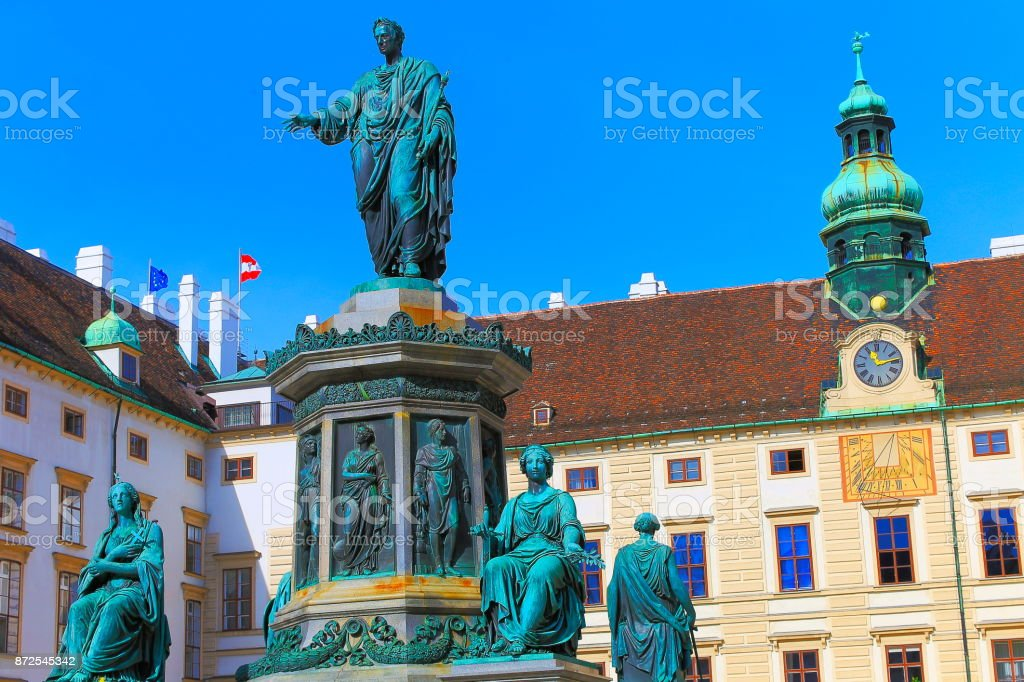 Beautiful monument to Franz Joseph I of Austria on Amalienburg - Vienna Cityscape panorama, with  impressive rococo and reinassance building architecture and urban skyline at clear sky – Austrian and Euro flags - Vienna , Austria stock photo