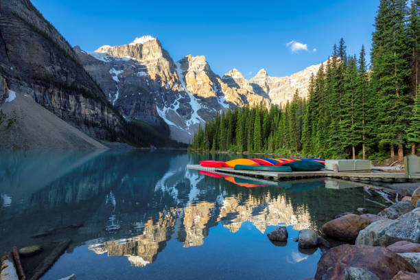 Beautiful Moraine lake in Banff National Park, Canada Beautiful sunrise under turquoise waters of the Moraine lake with snow-covered peaks above it in Canadian Rockies,  Banff National Park, Canada emerald lake stock pictures, royalty-free photos & images